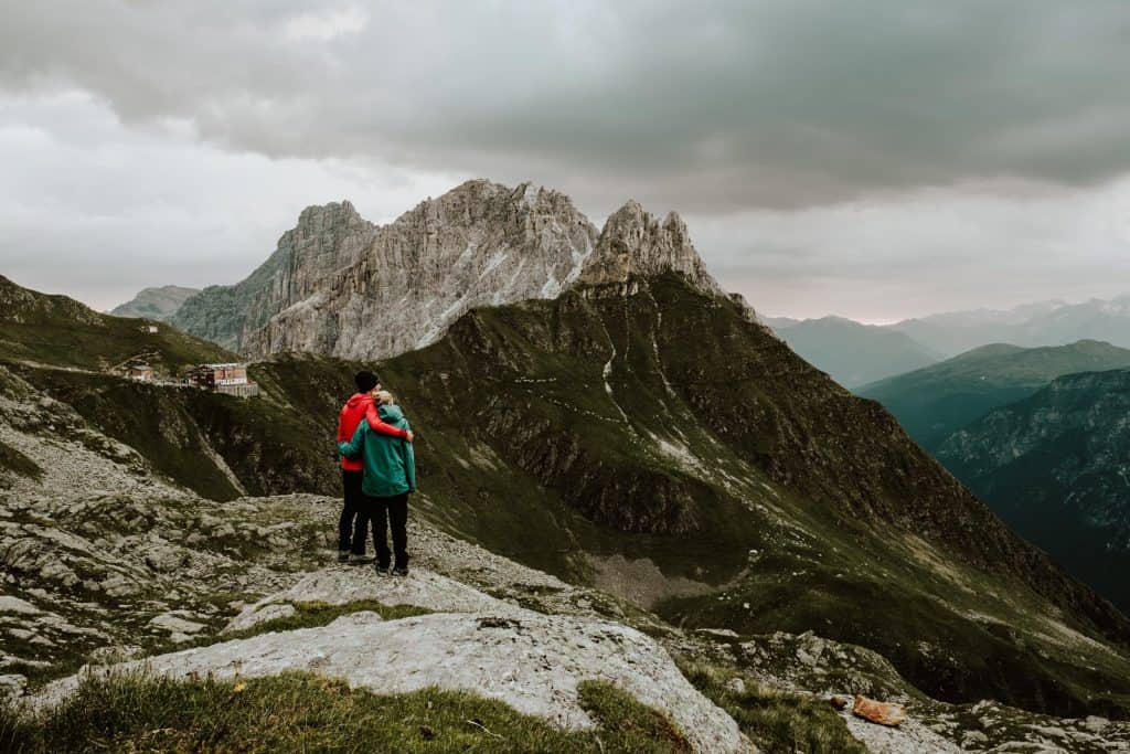 Couple standing on a mountain top looking out at the mountains