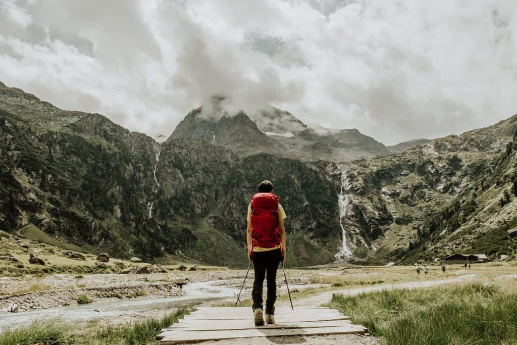 Man with red backpack hiking in the Alps
