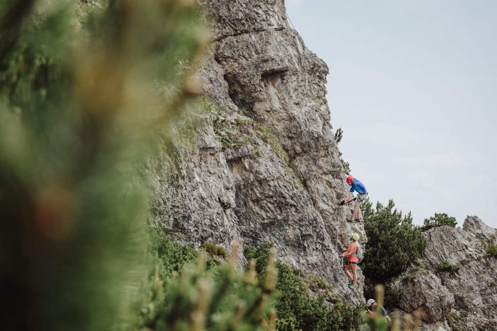 three people climbing up a via ferrata on rock face in the alps