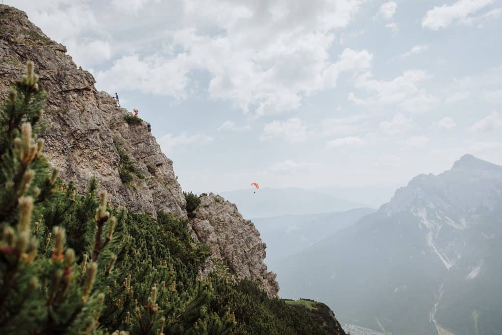 The climbers on a via ferrata in the Austrian Alps with a paraglider in the distance