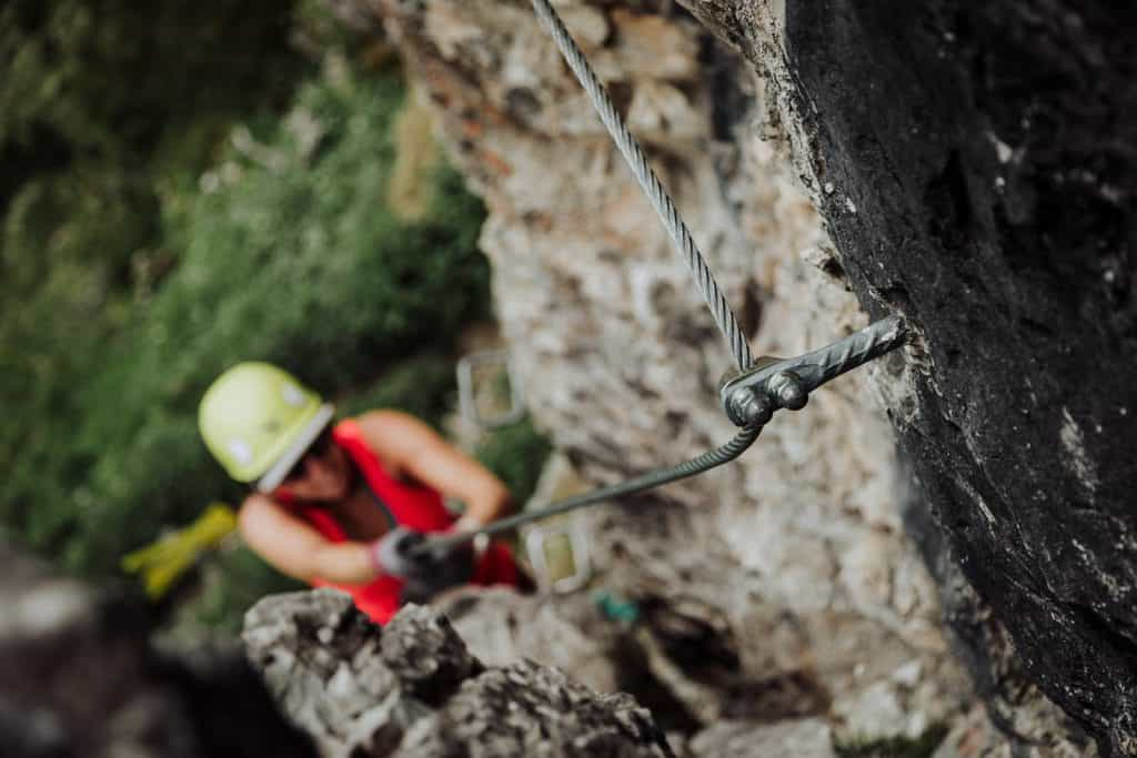 Woman (out of focus) climbing up steel via ferrata cable (in focus)