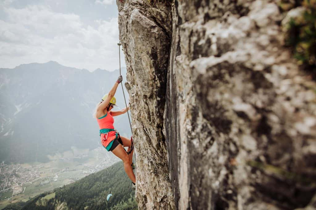 Blonde woman on a via ferrata cliff edge in the Austrian Alps