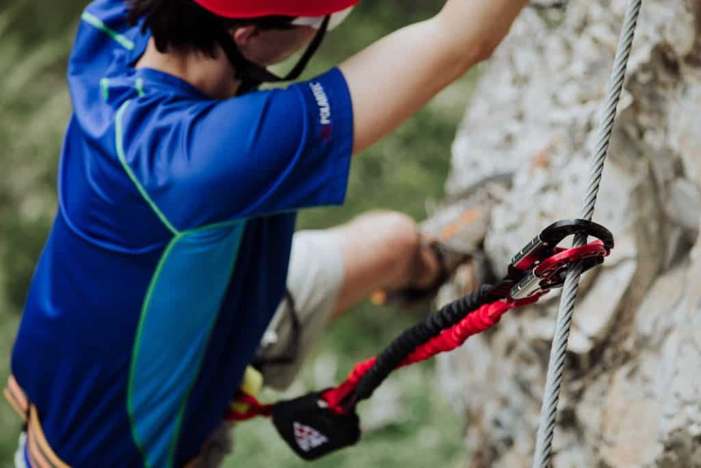 Close up showing the dual carabiners and shock absorber of a via ferrata set in action